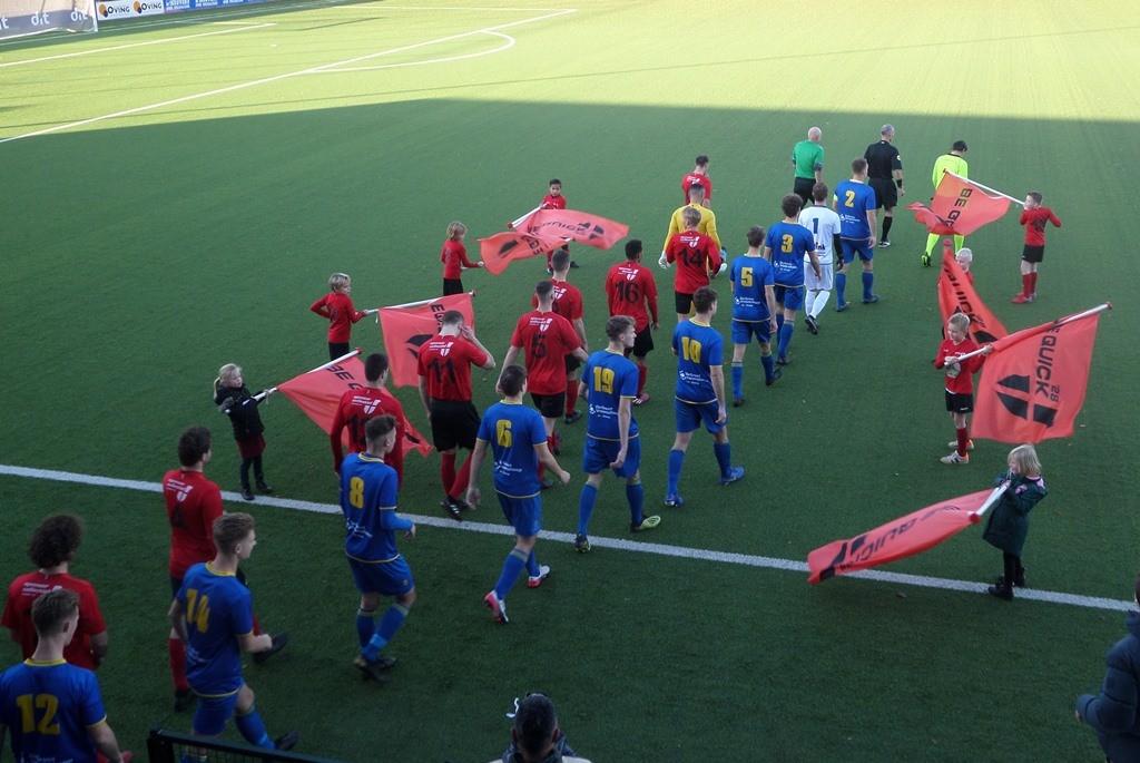 De opkomst van de spelers, geflankeerd door jeugdige Be Quickertjes.
